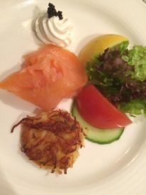 Smoked salmon arranged with potato pancakes and crispy garden lettuce